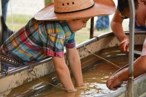 A boy in a cowboy hat plays in a tank full of water at Frontier Village at Cheyenne Frontier Days.