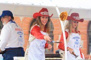Rodeo queens dressed in red hats flip pancakes at the free pancake breakfast at Cheyenne Frontier Days.