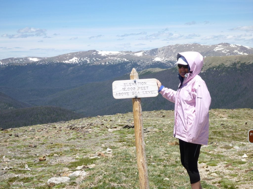 Trisha Poses in the summer on a high-altitude pass with a sign that says 12,000 feet above sea level.