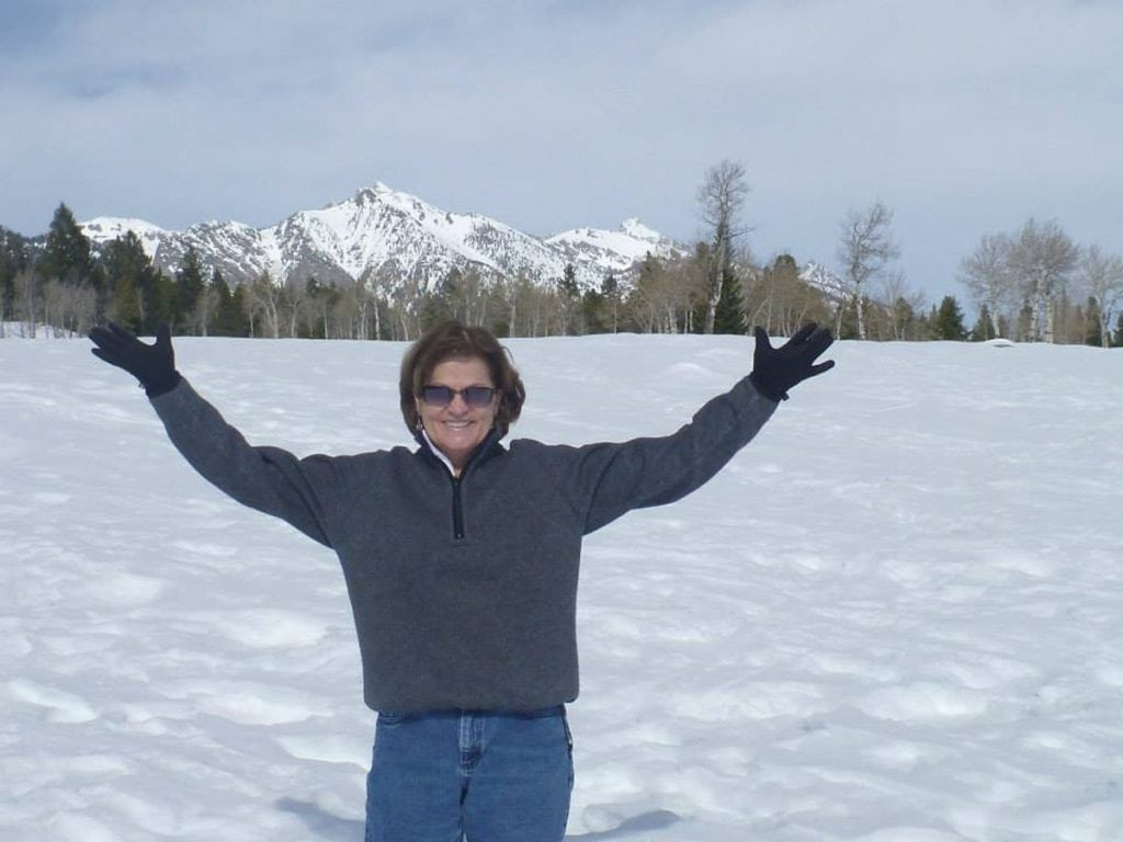 Trish Washburn holds her hands out in a snowy landscape with a mountain behind her. Washburn is passionate about skiing. Thanks to help from a psychologsit at the UCHealth primary care clinic close to her home, she's regaining her confidence on the slopes. Photo courtesy of Trisha Washburn.