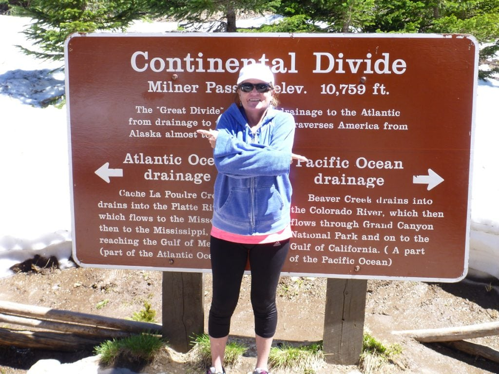 Trisha poses with a Continental Divide sign at the top of a pass. She is new to Colorado and is trying to cope with anxiety after an Alzheimer's diagnosis.