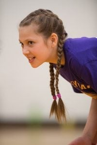 An 11-year-old girl anticipates a volleyball serve from opposing team
