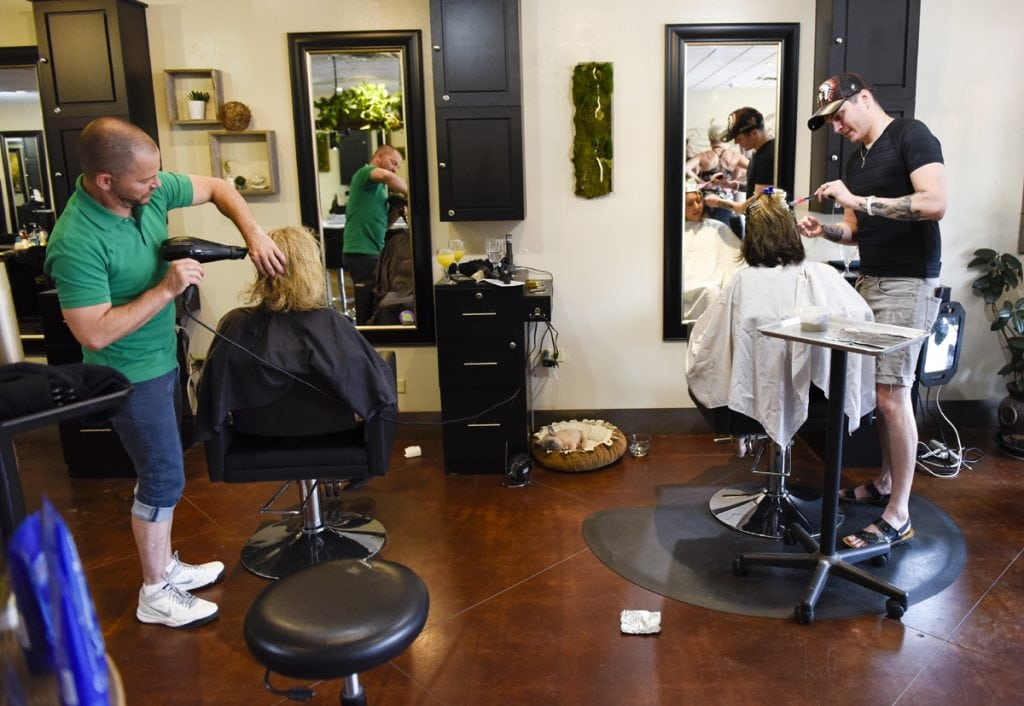 Newly married, Stephen Estrada and Kenley Erskine also work side by side in a hair salon. Here they are both doing hair for women.
