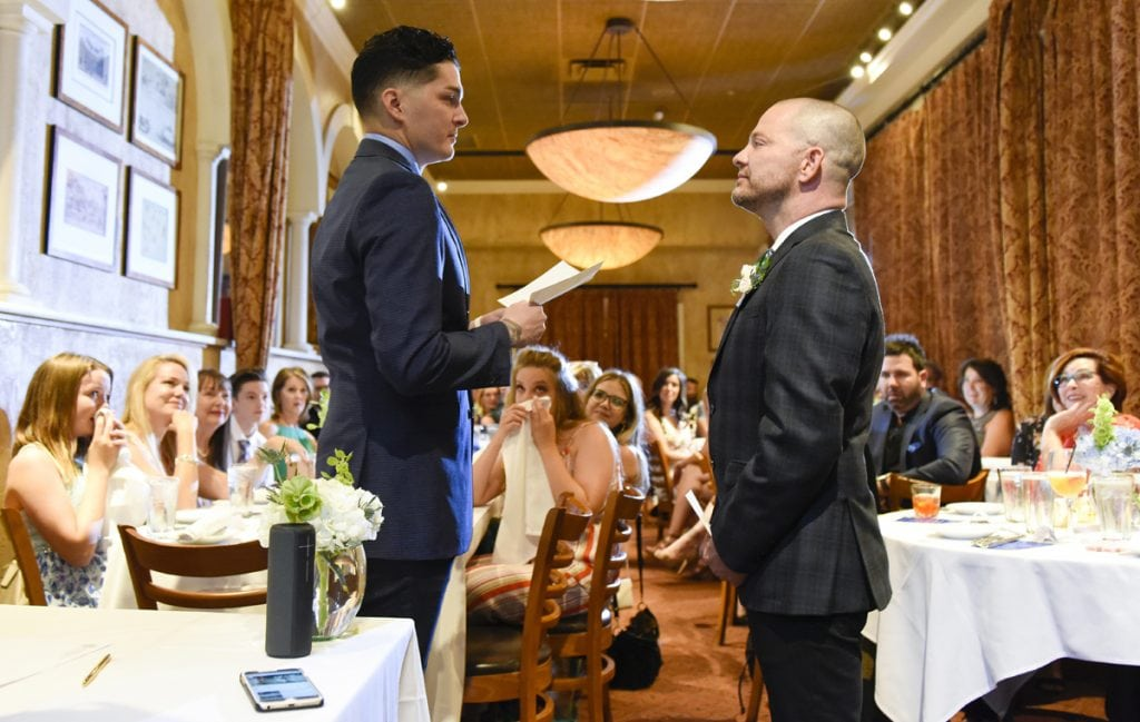 Guests wipe their eyes as Stephen Estrada and Kenley Erskine say their wedding vows at a Denver restaurant.