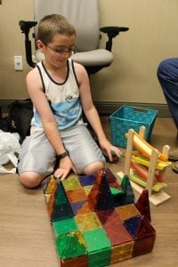 A young boy plays with magnetic tiles.