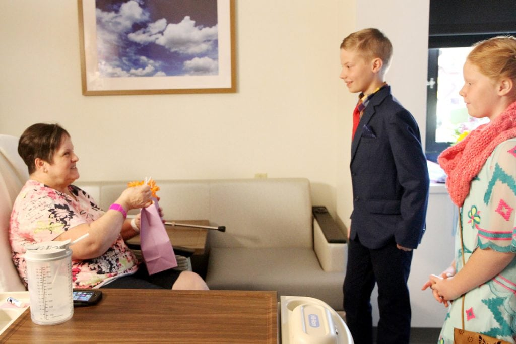 Charlie and his sister talk with a patient in her room.