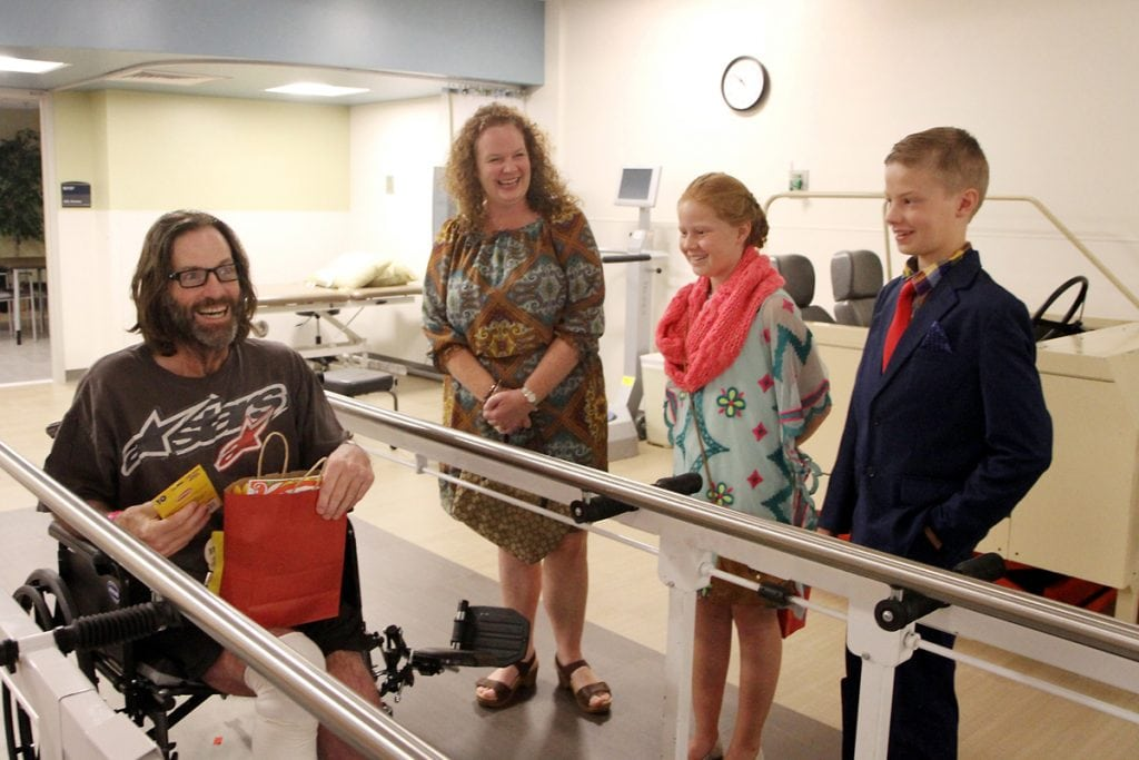 A patient laughs with charlie and his family.