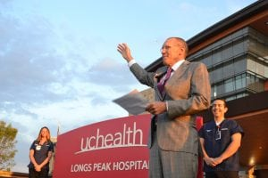 UCHealth Longs Peak Hospital president and CEO gestures with his hand as he shares inspiring remarks in front of a hospital on opening day.