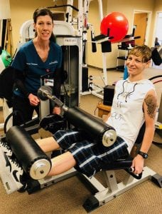 A physical therapist watches as a patient lifts weights with her legs during a physical therapy session.