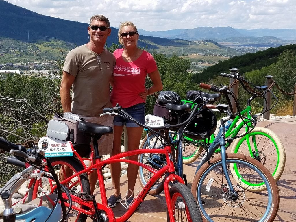Scott and Ramona Rudis pose for a photo behind bicycles | Bike helmet safety | UCHealth