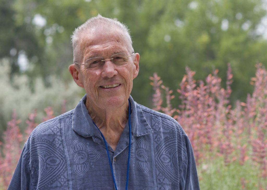 Portrait of Bill Brennan who has achieved a new lease on life after CAR-T immuontherapy treatment for blood cancer. He poses with some flowers behind him.