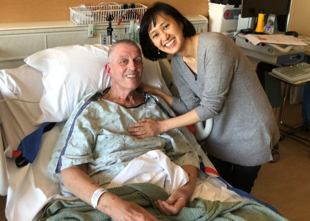 Bill Brennan in his hospital bed with his doctor, Enkhsetseg Purev, who helped him with CAR-T immunotherapy for deadly blood cancer.