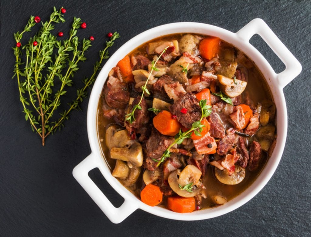 a pot of Burgundy Beef and Vegetable Stew on a black tile with a sprig of herbs next to it