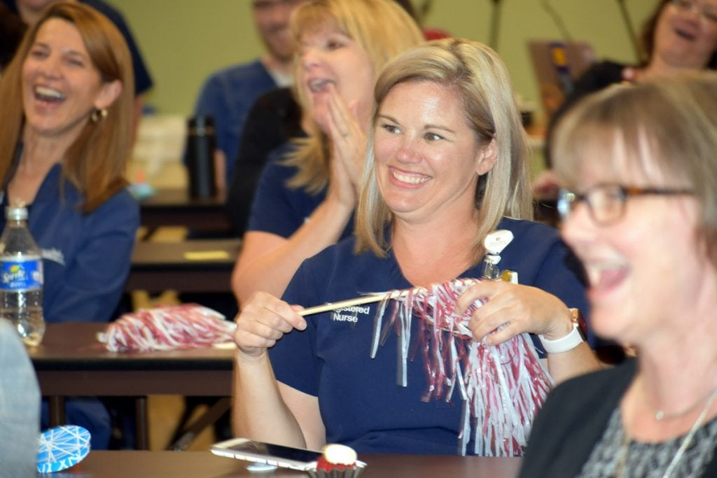 Nurse smiles and holds on to a pom pom as a group gathers to hear the official announcement that Poudre Valley Hospital achieved Magnet status for the fifth time.