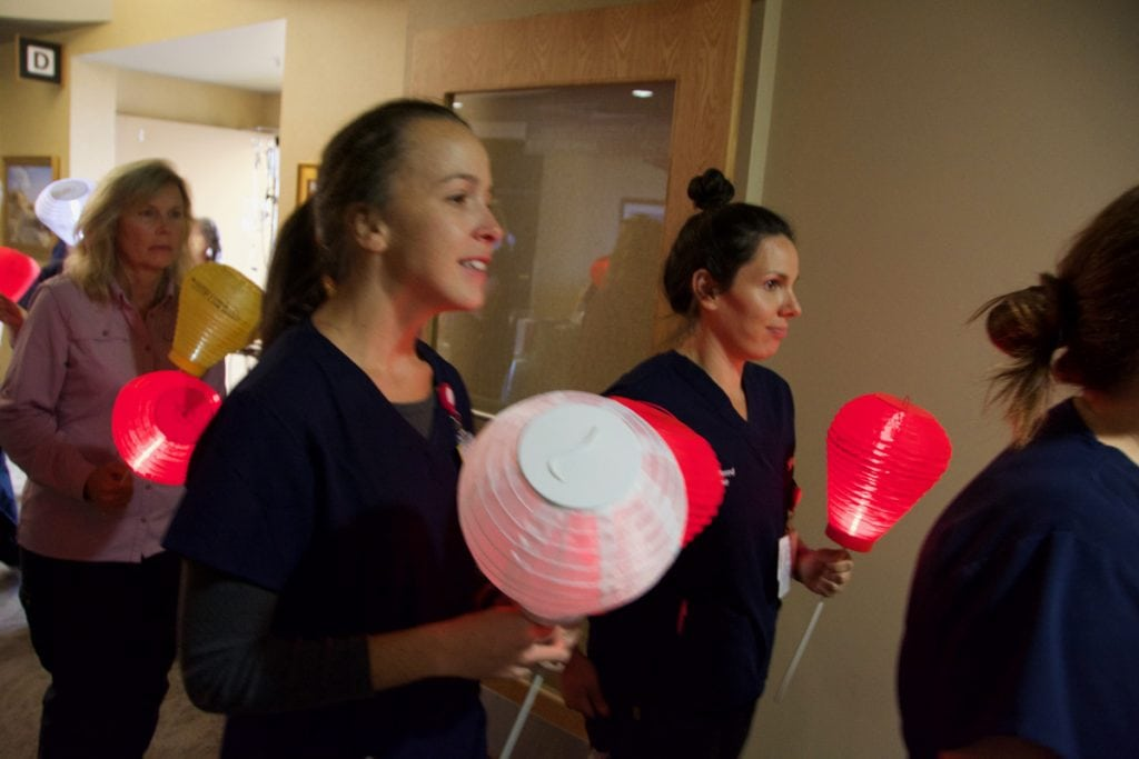 Nurses hold red and white lanterns as they walk down a dark hallway to support awareness about blood cancers and the Light the Night fundraiser for blood cancers.