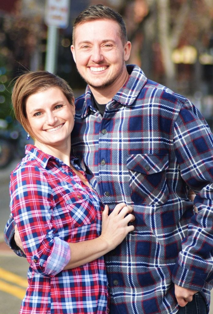 A copule poses for a photo. They were flannel shirts. On the left is a woman. On the right is Mal Foust, a transgender male. He's got a scruffy beard and is much taller than his partner.