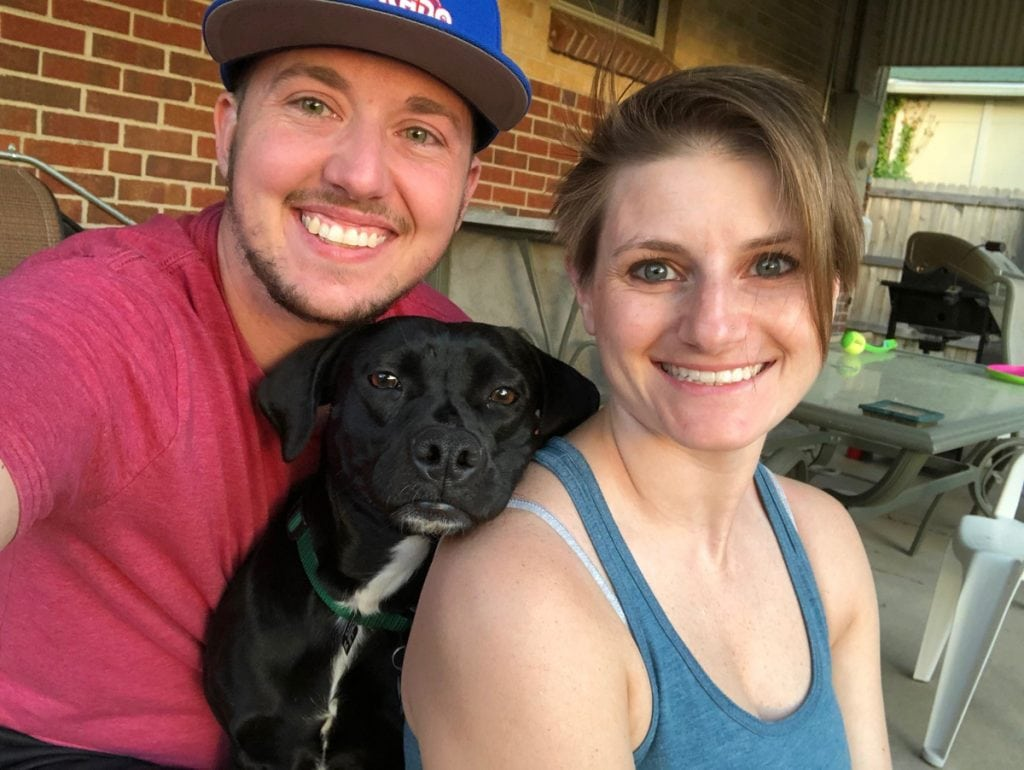 A couple poses with their dog in the middle.