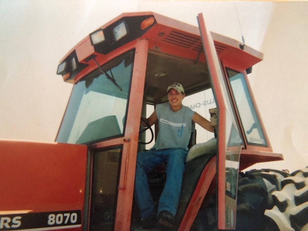 A teen sits in the cab of a large orange tractor. Mal Foust looks male and wears a ball cap, jeans and T-shirt. But he had been born a girl.