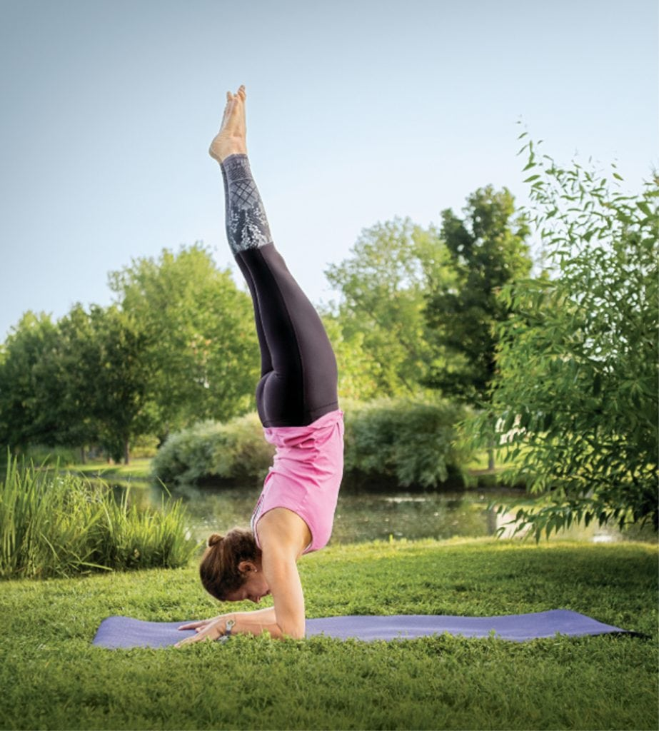 Breasst cancer survivor Louisa Drouet does a vertical yoga pose with gardens in the background.