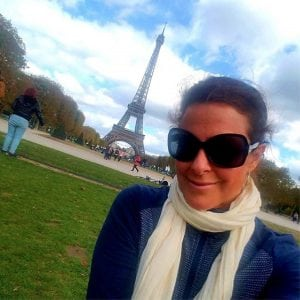 "Louisa Drouet poses in Paris with the Eiffel Tour behind her. She is celebrating her breast cancer recovery with a ""world victory tour."""