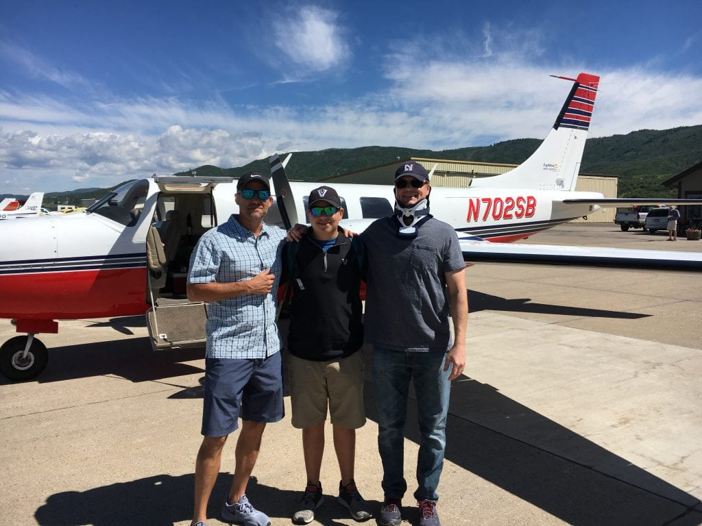 Brian Malek poses with his brother-in-law and nephew in front of an airplane during Brian's recovery from a spinal cord injury..