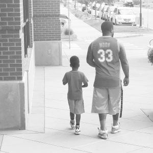 Photo of David Kenyatta and his son, who is 5. You see the two of them from behind.