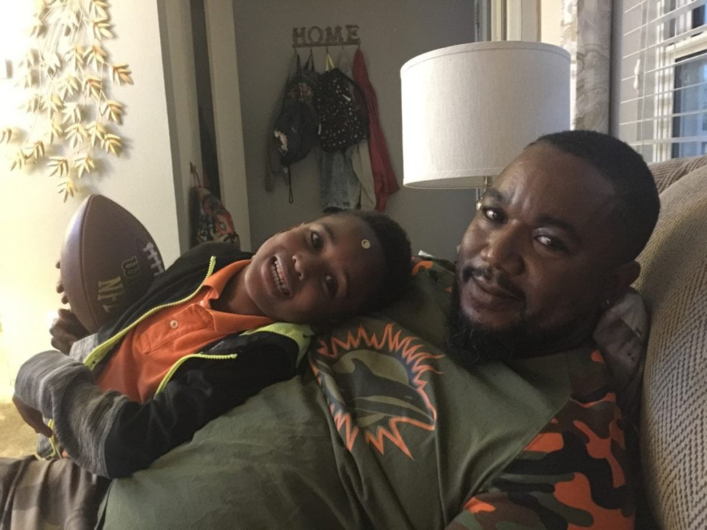 David Kenyatta cuddling with his son, DJ.