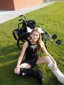 A young woman sits in grass with her wheel chair behind her.