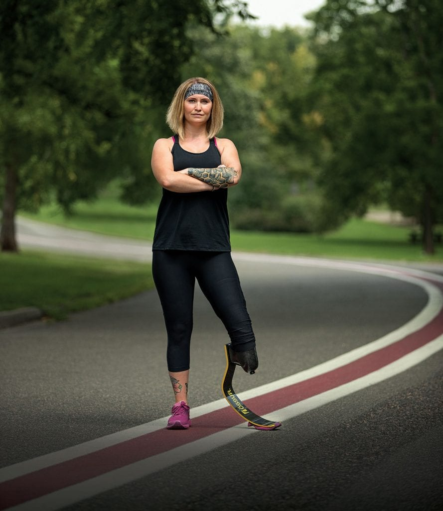 Alina Miller had to jump four stories out of her burning apartment building. Now, she's embracing every adventure that comes her way. She poses here with a road. Alina had to have one leg amputated and runs with a blade.