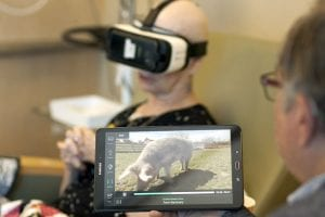 patient using virtual reality in health care setting while husband runs tablet.