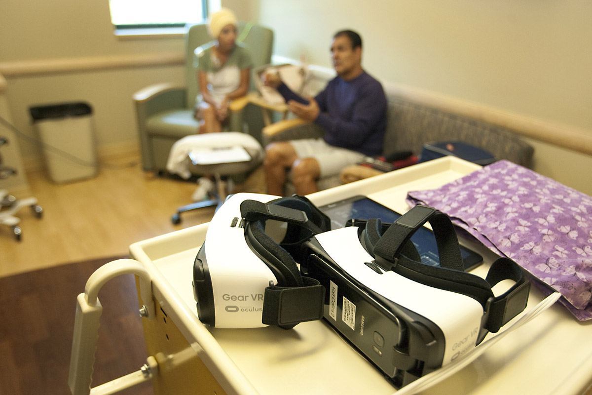 virtual reality googles sit on a table while couple talks in the background.