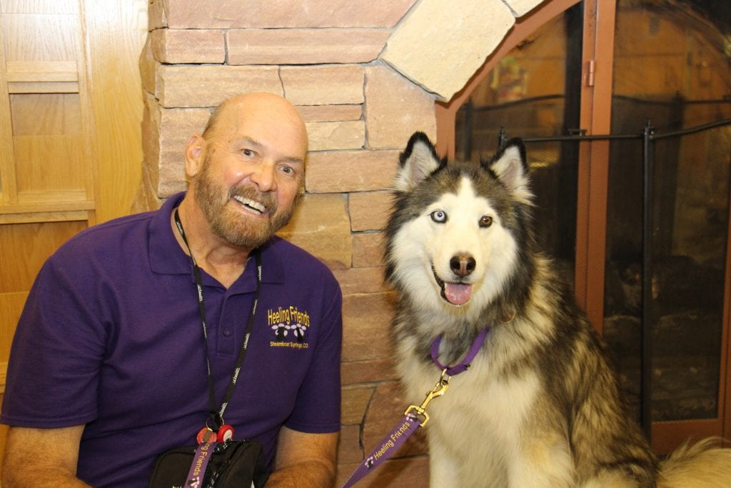 Bob Tomsky and his six-year-old husky, Anok, are pictured near the fireplace at UCHealth Yampa Valley Medical Center.