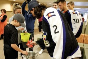 Boy transfers Halloween candy from Kelly Cup trophy to a Halloween trick-or-treating bucket.