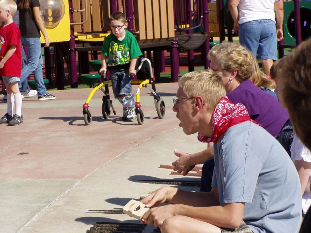 "A boy using a walker plays at Inspiration Park in Fort Collins. In the foreground, some special needs teens also play at the park. It was designed to be ""universally accessible"""