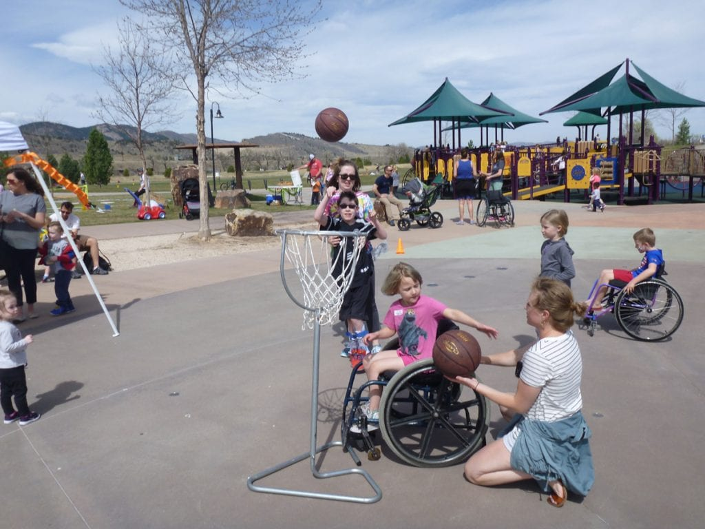 A child in a wheel chair plays basketball at a universally accessible park called Inspiration in For Collins.