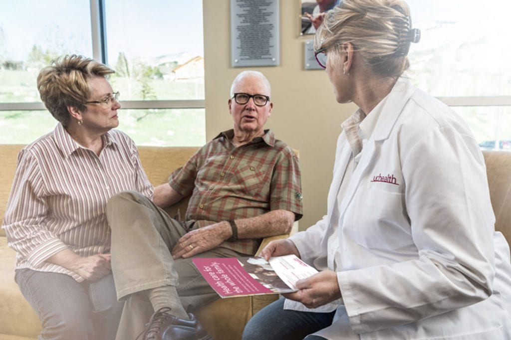 A UCHealth doctor talks to a couple about medical needs.