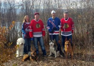 family with hockey jerseys and four dogs