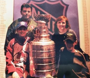 family standing with the Stanley cup