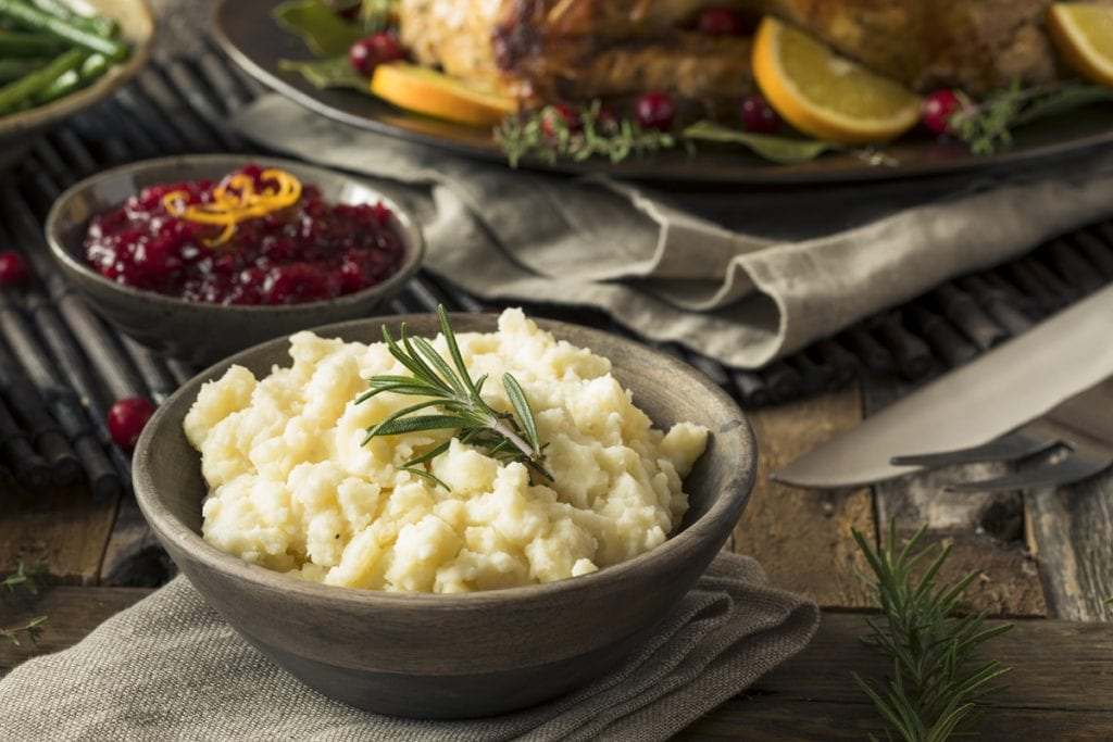mashed potatoes with a sprig of rosemary on top and cranberries and turkey visible in the bakcground