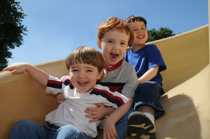 3 boys smiling as they come down a slide