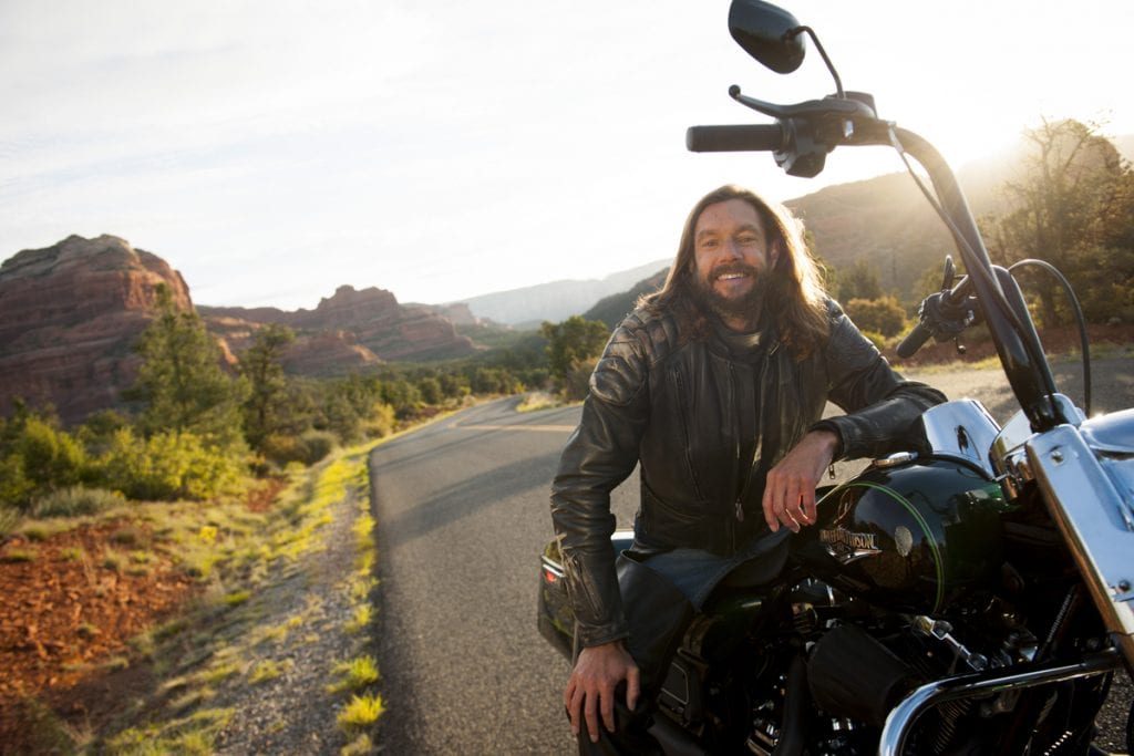A young man with long hair poses on his Harley with the red rocks of Sedona in the background.
