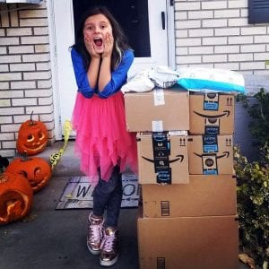 Marlie with a surprised face and a stack of boxes on her doorstep.
