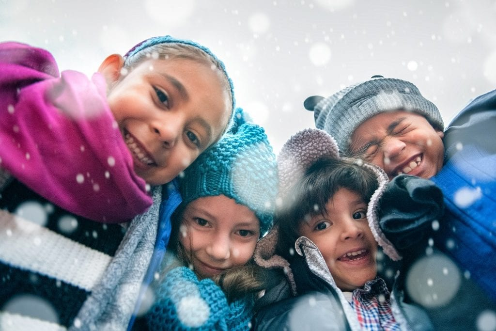 This photo shows children outside in warm coats and hats as snow begins to fall.