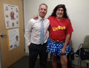 Dr. Petit and Rob, who is dressed in red shit and blue-starred tutu, and a black wig