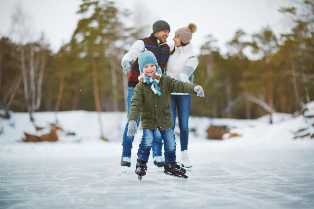 A boy ice skates on a pond in the mountains. He's grinning and his parents are smiling in the background.