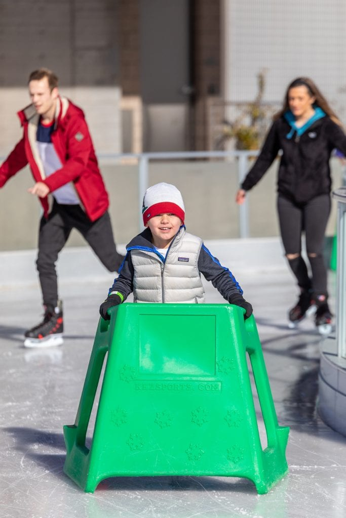 A child holds onto a green plastic walker as he learns to skate at the Parker Ice Trail at Discovery Park.
