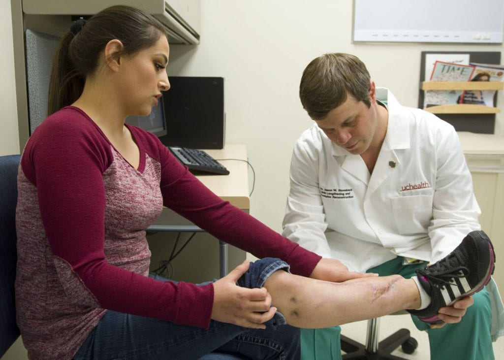 A physician examines a patient's injured leg.