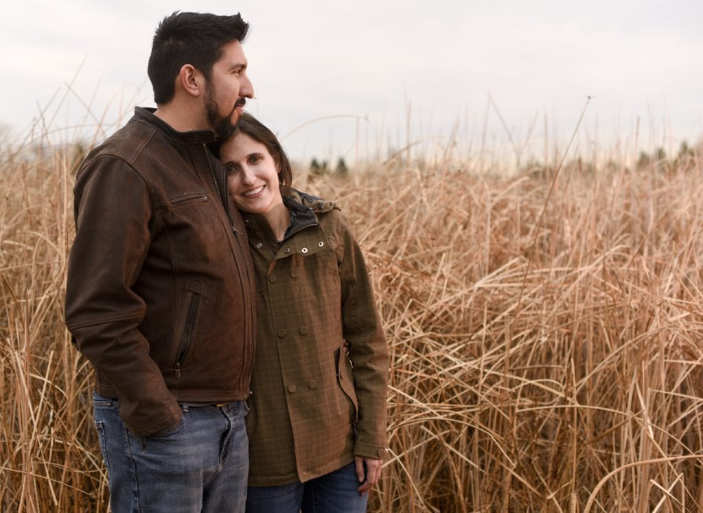 A woman and her husband pose for a picture near a wetland. He's hugging her. She survived a rare polio-like illness called AFM.