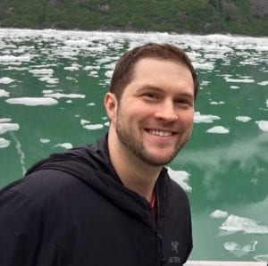 Dr. Dan Pastula is an expert in a disease called acute flaccid myelitis or AFM and helped recognize it when a virus attacked a young Lakewood mom. Here he poses on a trip to a lake with icebergs floating behind him.