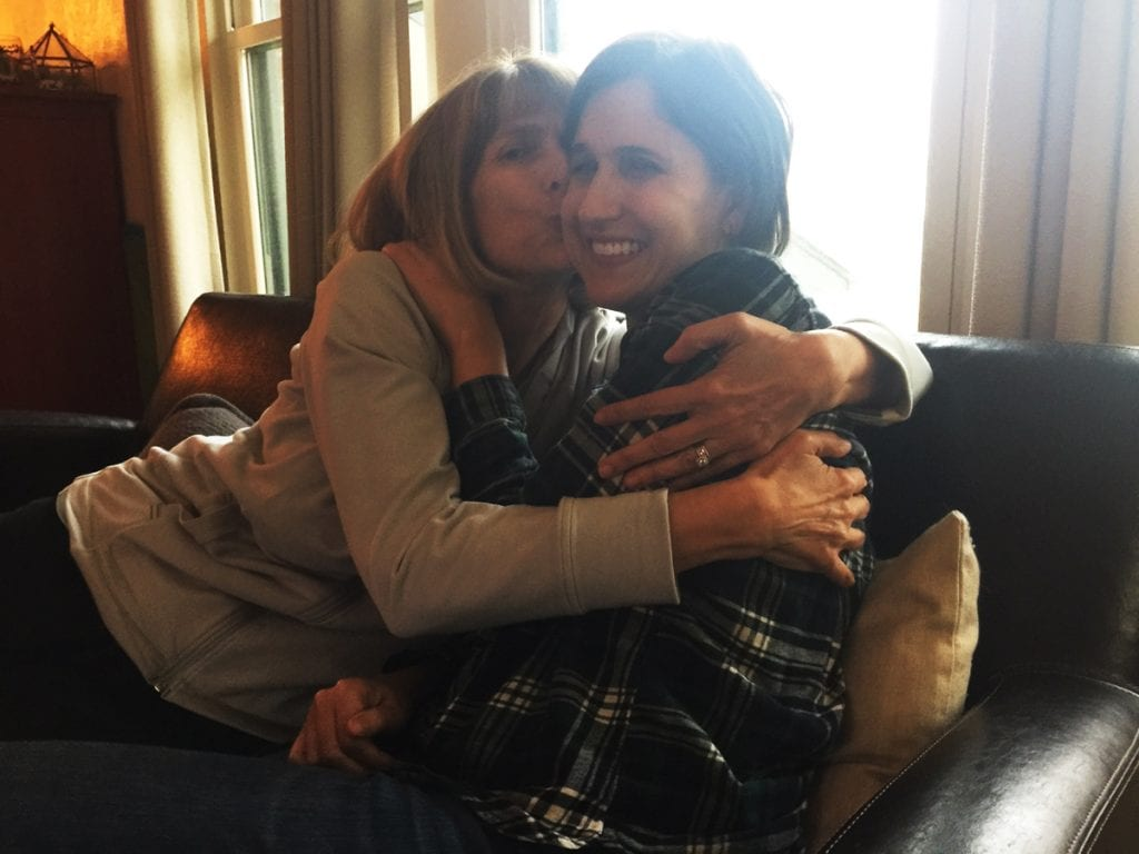 Besty Brock, left, hugs her daughter, Emily West. She's thrilled that her daughter is recovering from a rare polio-like illness caled AFM.